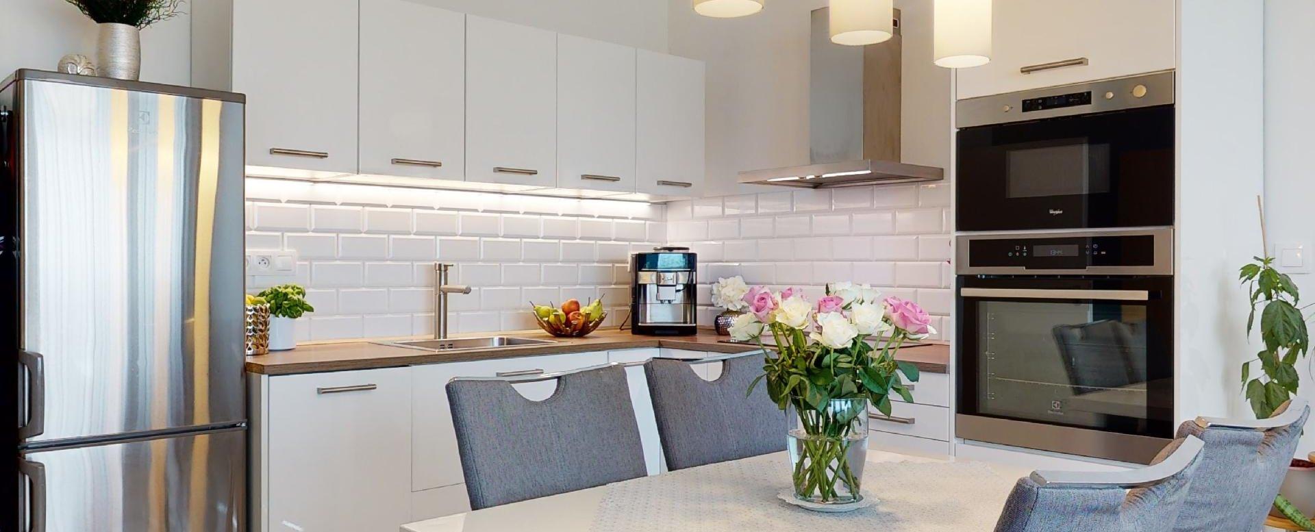 kuchynský stôl so stoličkami a kuchynská linka so spotrebičmi