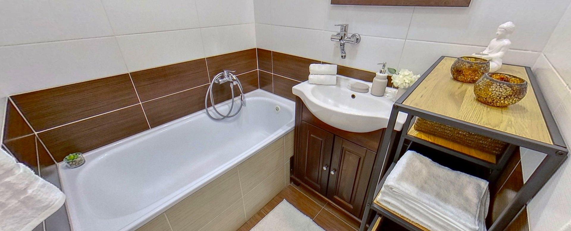 Pohľad na vaňu a umývadlo so skrinkou v kúpeľni