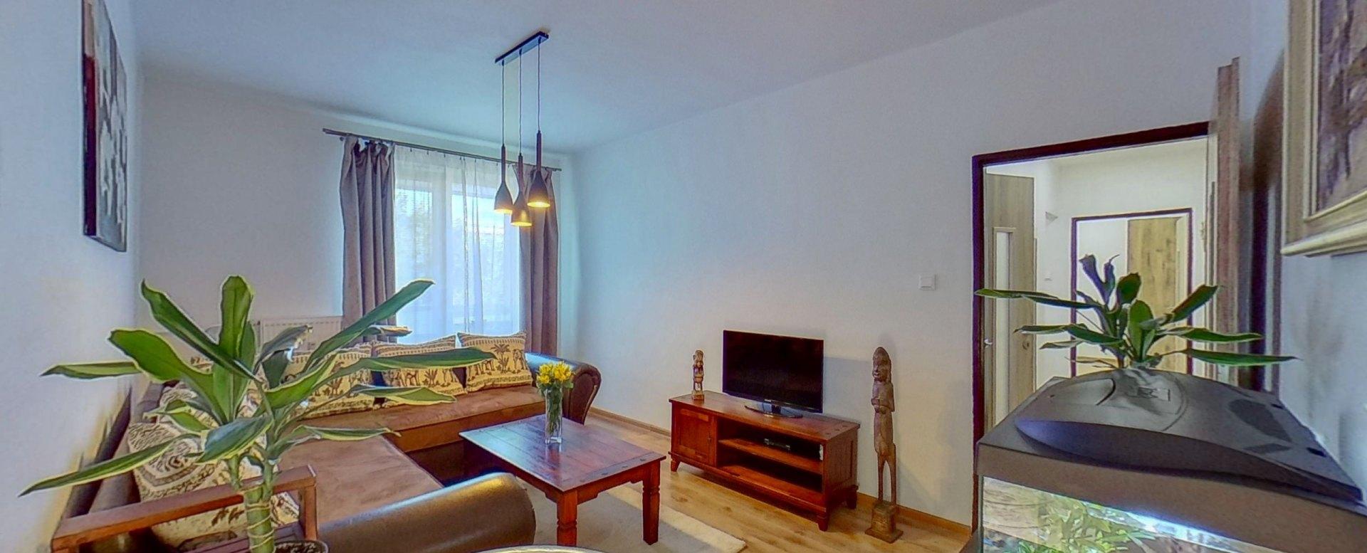 Pohľad v obývacej izbe na tv, kvet, akvárium a chodbu