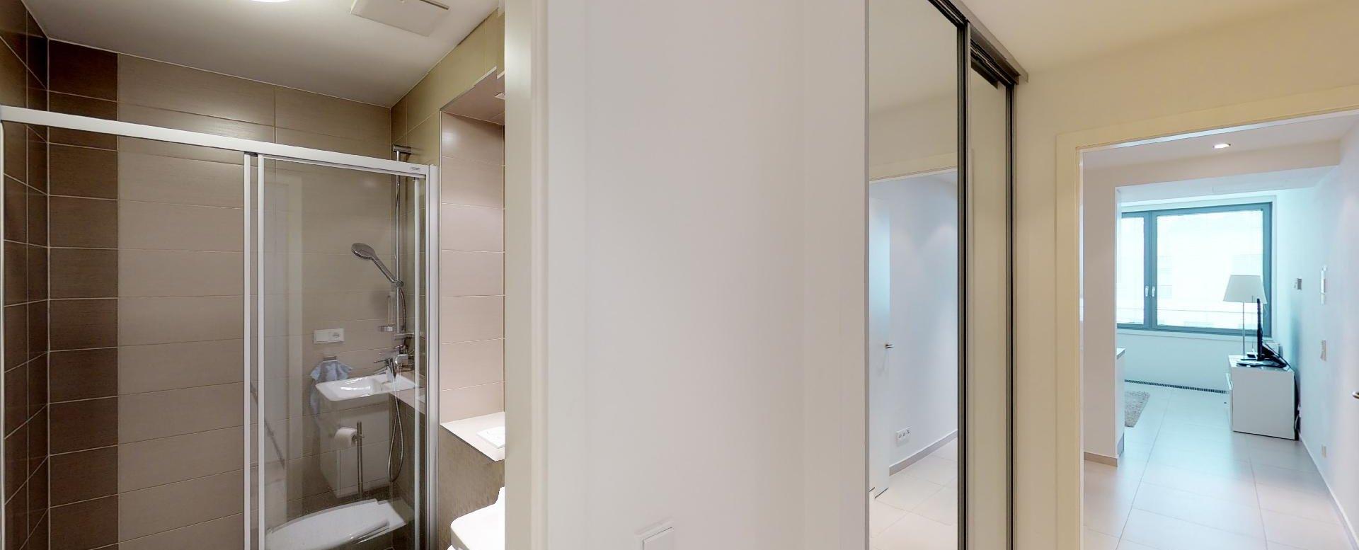 Kúpeľňa a chodba so stavanou skriňou v 2-izbovom byte v Eurovea Riverside
