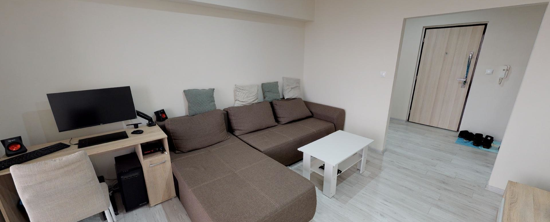 Obývacia izba s pracovným stolom a sedačkou v 2-izbovom byte na bulvári v Žiline