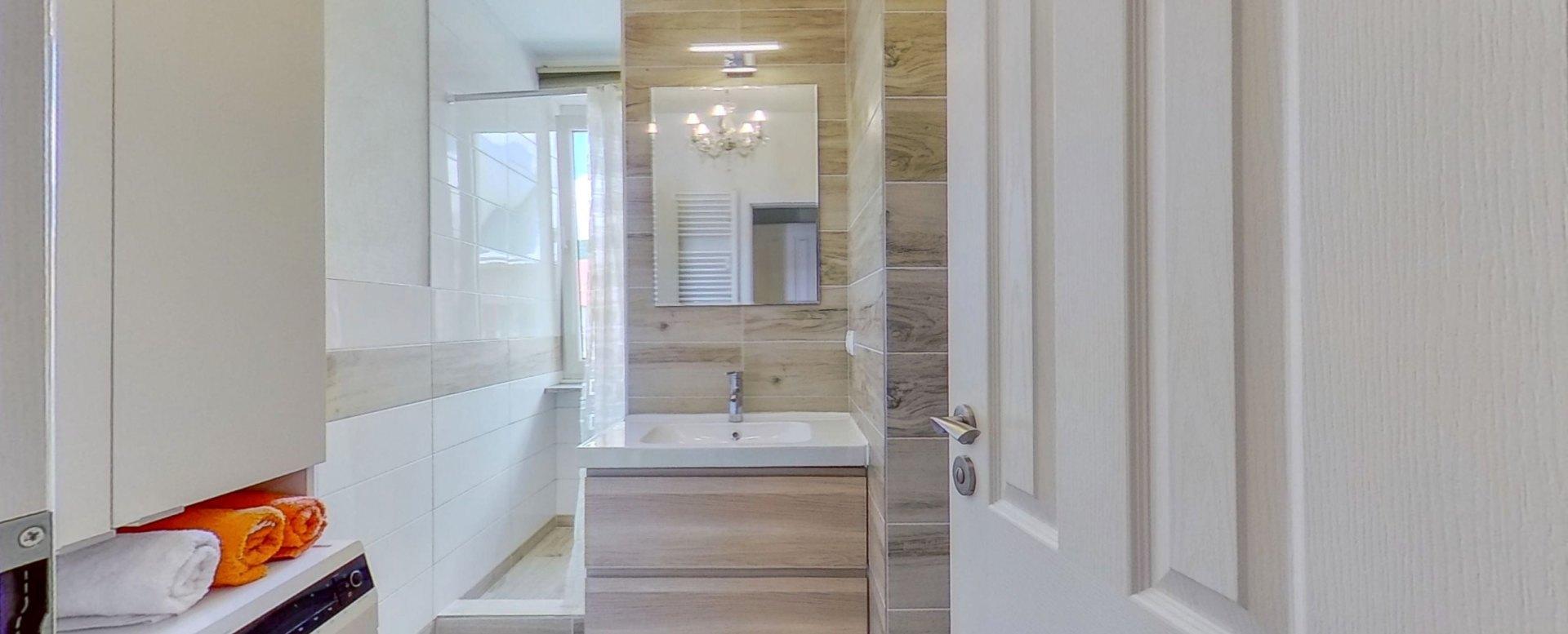Kúpeľňa so sprchovým kútom a práčkou