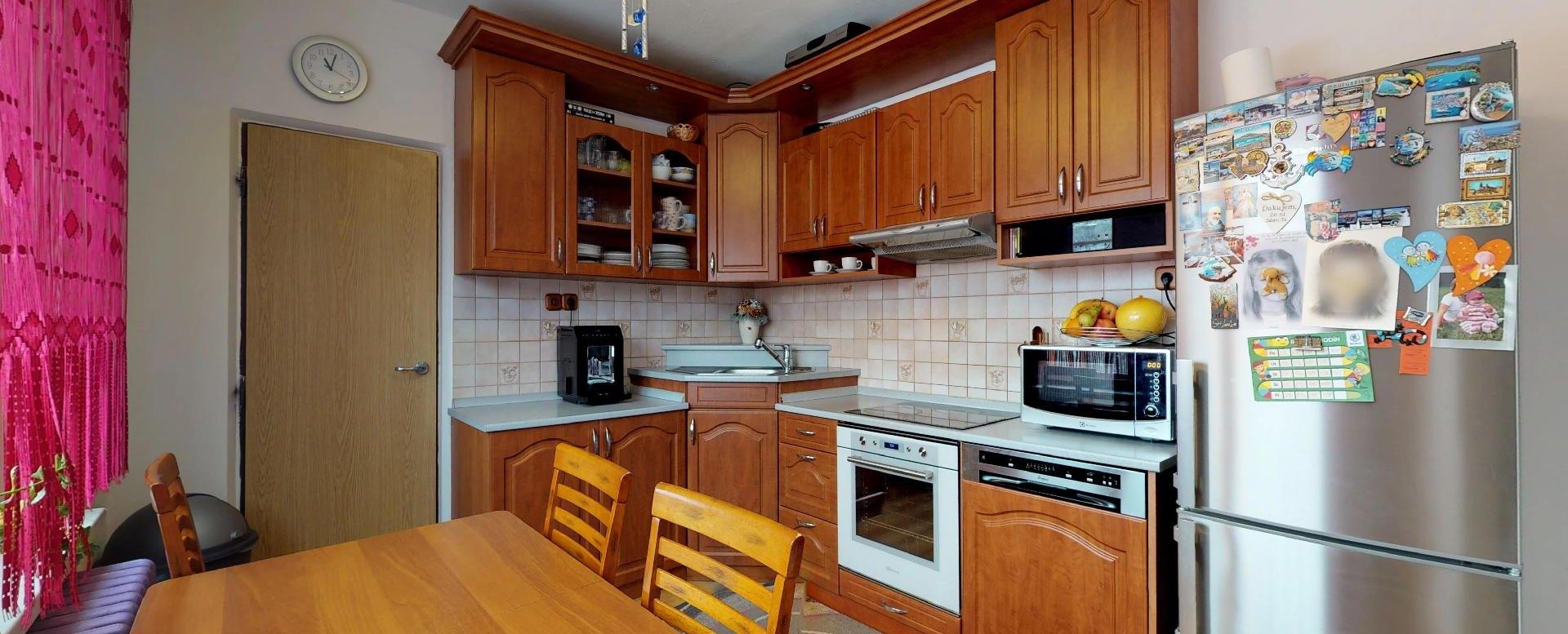 Pohľad na kuchynský stôl, kuchynskú linku, chladničku a špajzu