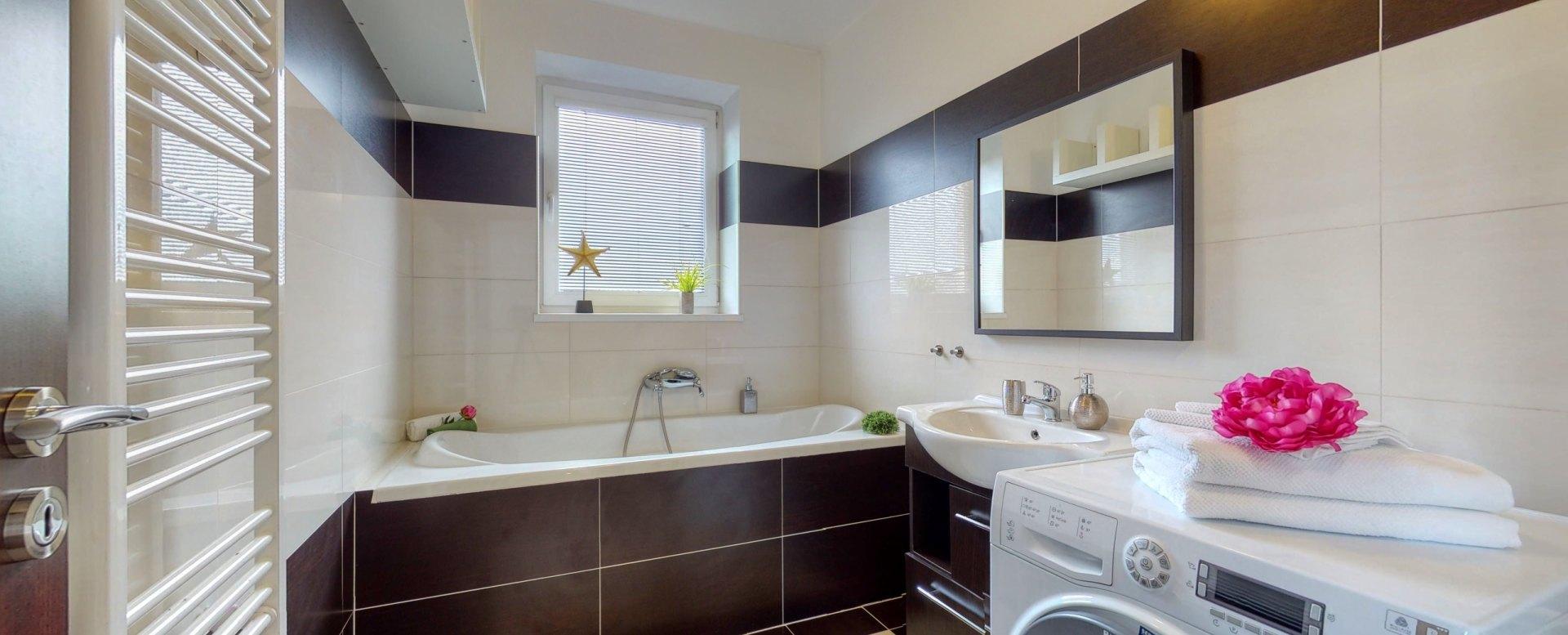 Pohľad do kúpeľne s vaňou a práčkou