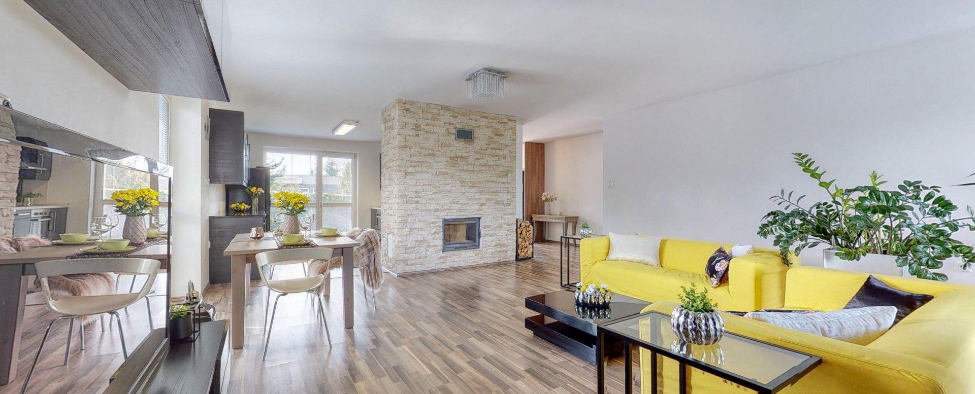 Pohľad v obývacej izbe na krb, jedálensky stôl, krb a sedaciu súpravu