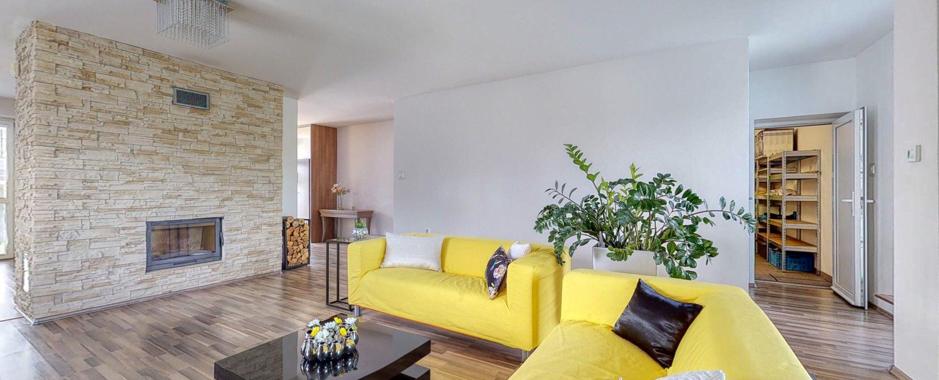Pohľad v obývacej izbe na krb, konferenčný stolík so sedaciou súpravou a vstup do garáže