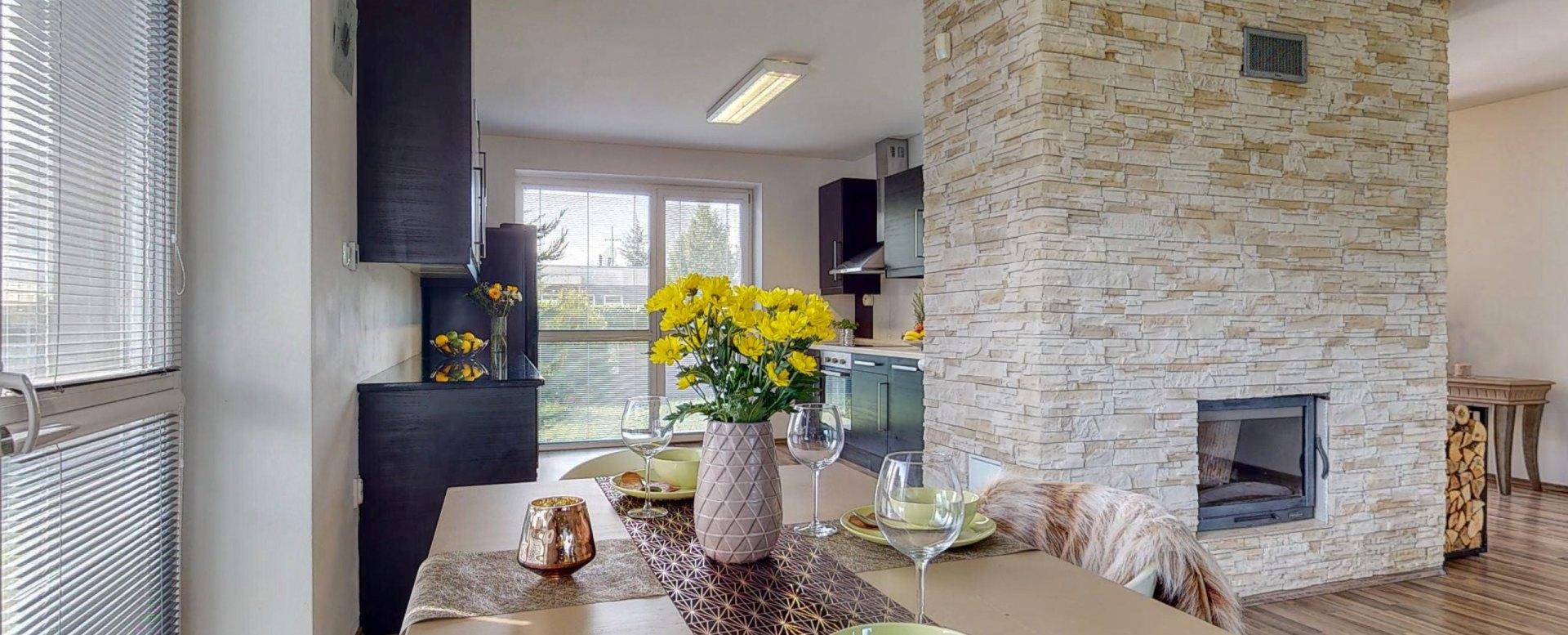 Pohľad na jedálenský stôl, kuchyňu a krb