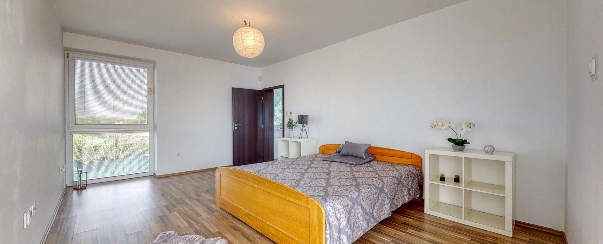 Pohľad na manželskú posteľ, okno a vstup do spálne