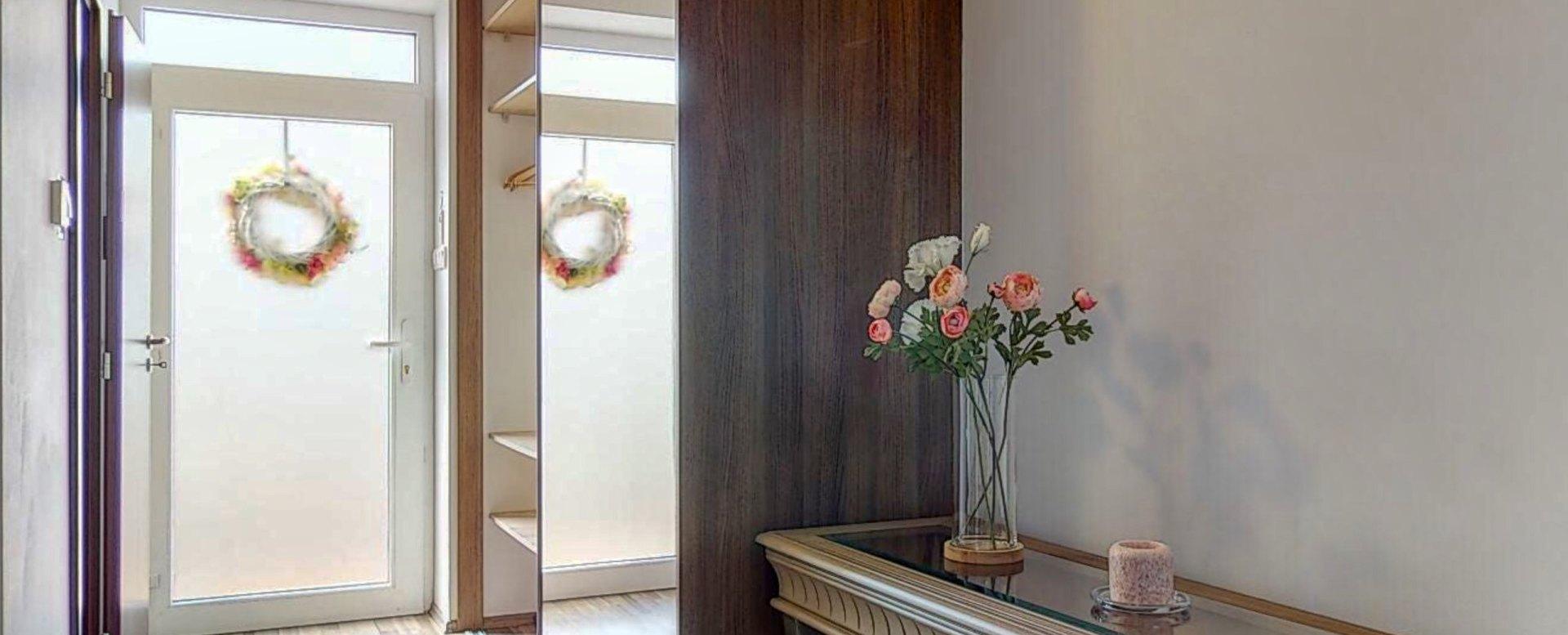 Pohľad na vstavanú skriňu, stolík s kvetinou a vstup do domu