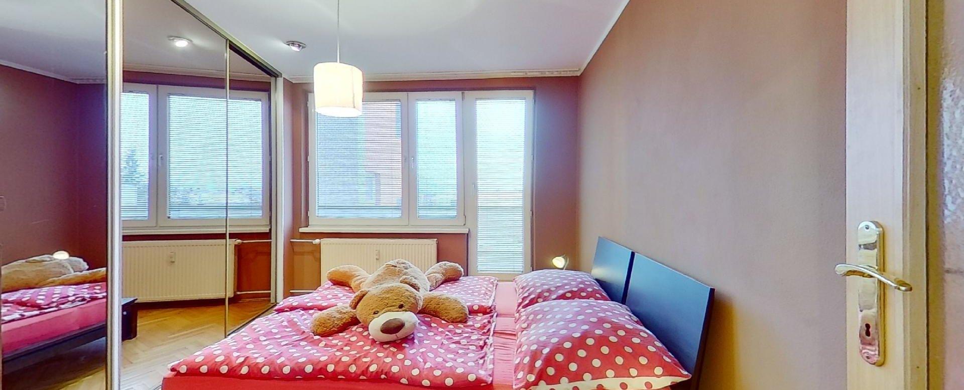 pohľad na manželskú posteľ, vstavanú skriňu a lodžiu v spálni
