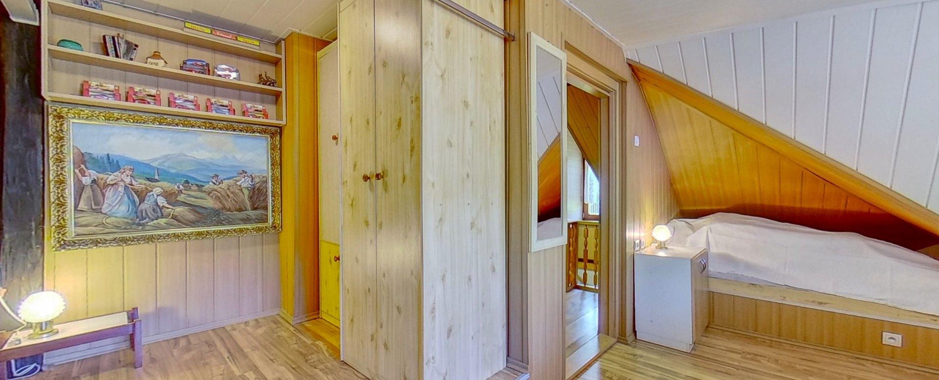 Obraz, poličky a skrine v podkrovnej izbe