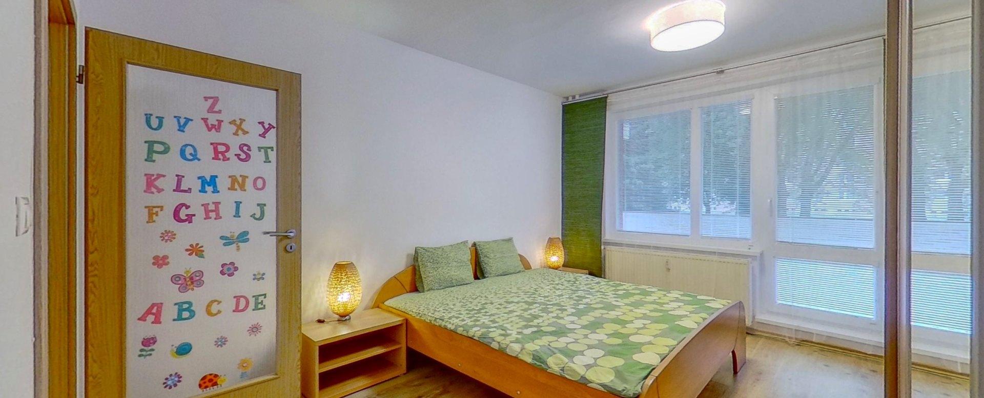 Pohľad na manželskú posteľ a lodžiu v spálni