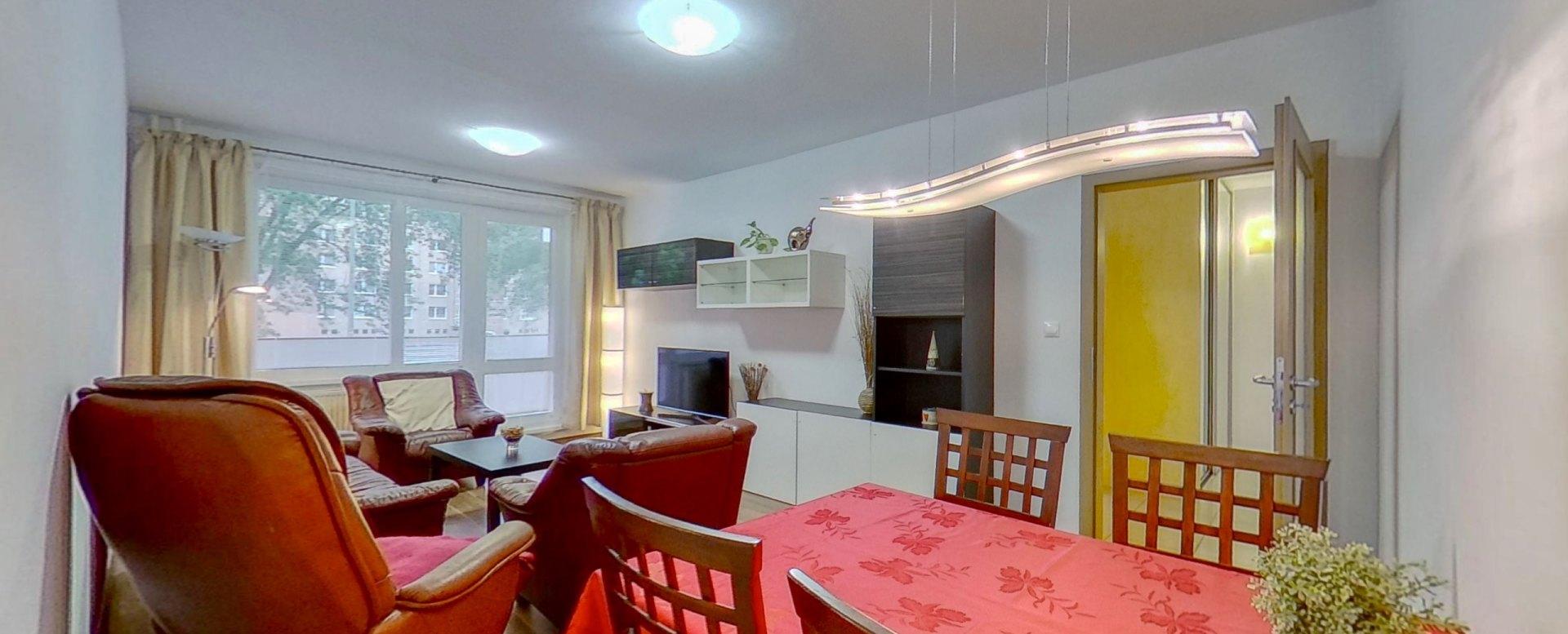 Pohľad na jedálensky stôl, kreslo a vstup do obývacej izby