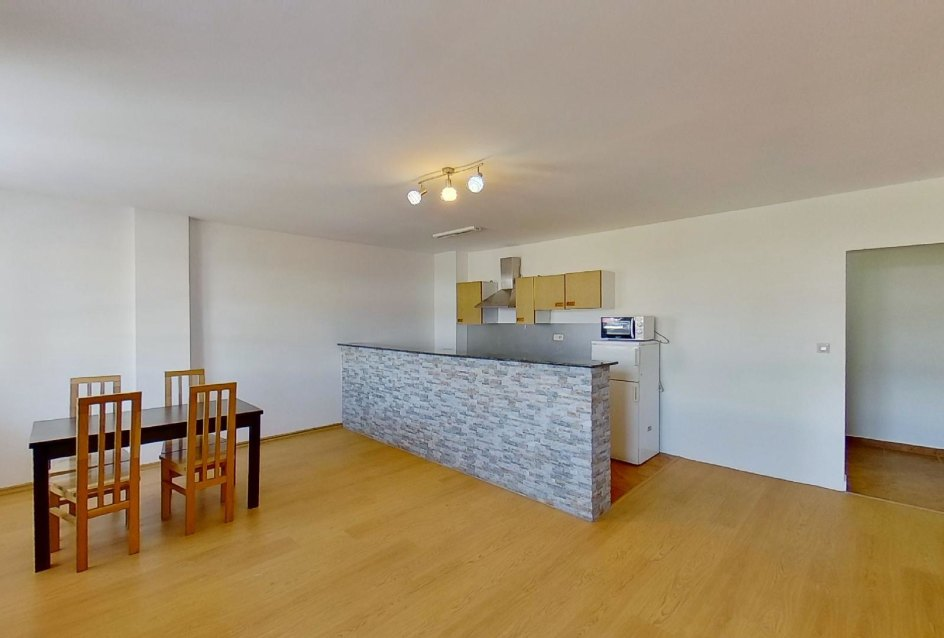 obývacia izba s jedálenským stolom a kuchynským kútom