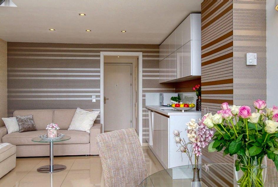 Váza s kvetinami, sediacia súprava, kuchynský kút a vstup do bytu