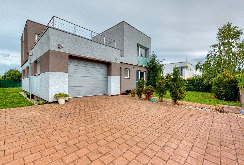 Pohľad na rodinný dom s garážou, terasou a záhradou
