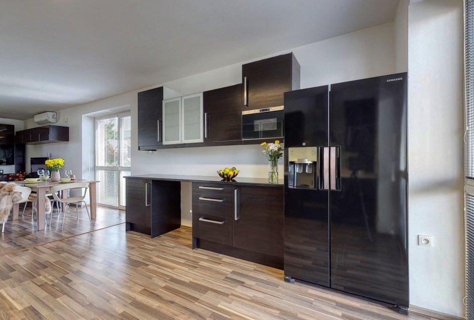 Pohľad v kuchyni na chladničku a druhú časť kuchynskej linky