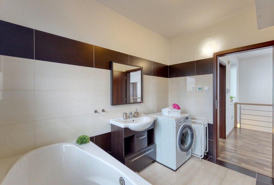 Pohľad na umývadlo so skrinkou a práčku