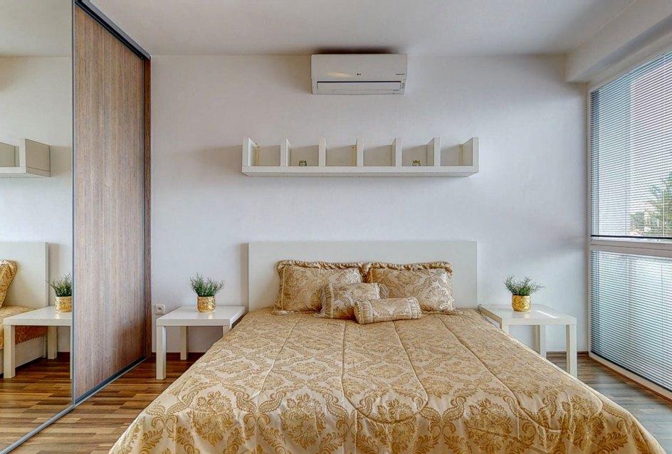 Pohľad na manželskú posteľ a vstavanú skriňu so zrkadlom