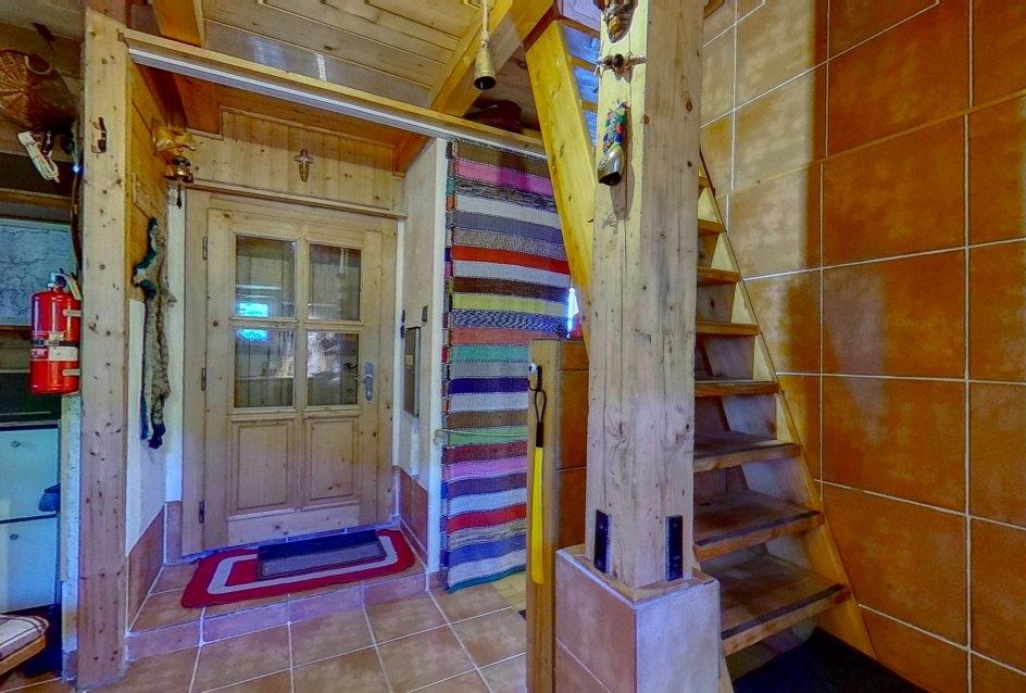 Pohľad na vstup do drevenice a schodisko na povaľu