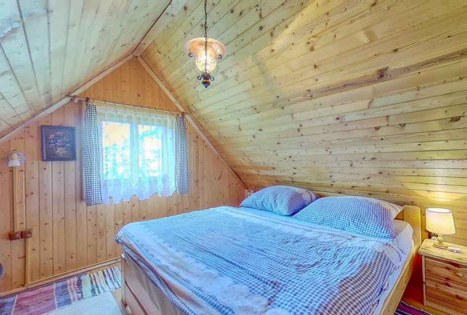 Pohľad na manželskú posteľ so stolíkmi v podkroví