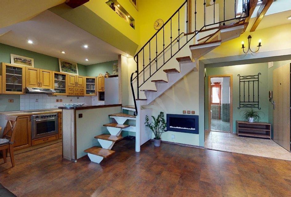 Obývacia izba s kuchynským kútom a schodiskom na druhé podlažie