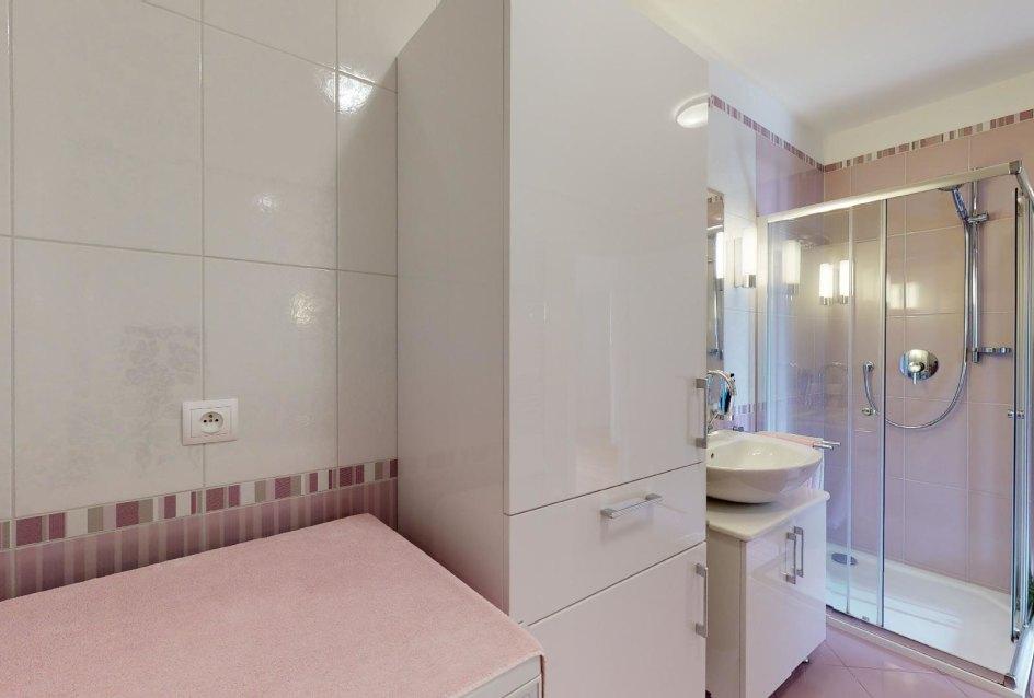 pohľad na práčku, kúpeľňový nábytok, umývadlo a sprchový kút