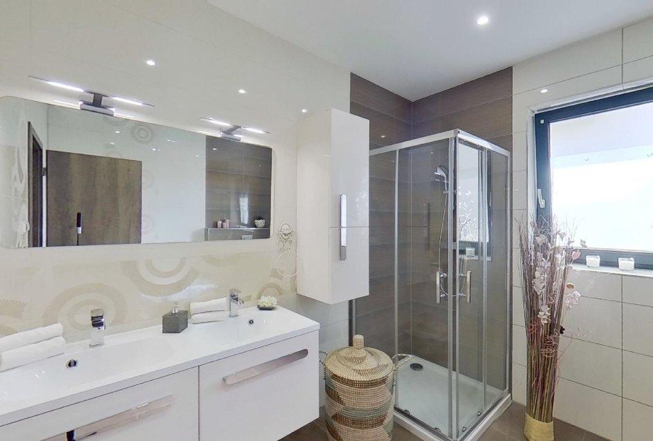pohľad na umývadla, zrkadlo a sprchový kút