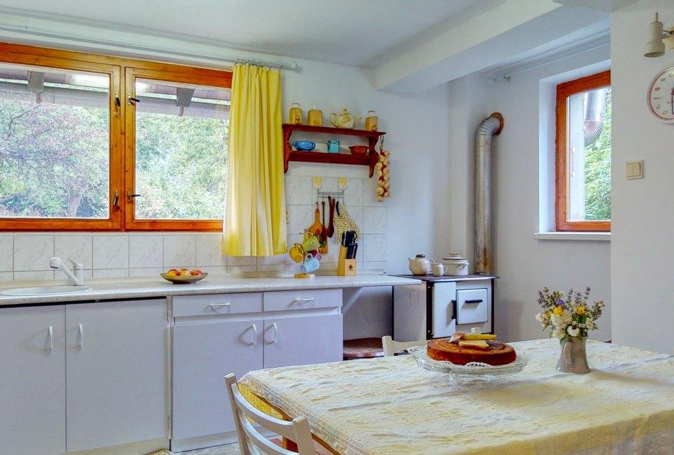 Pohĺad na kuchynský stôl, okno a kuchynskú linku