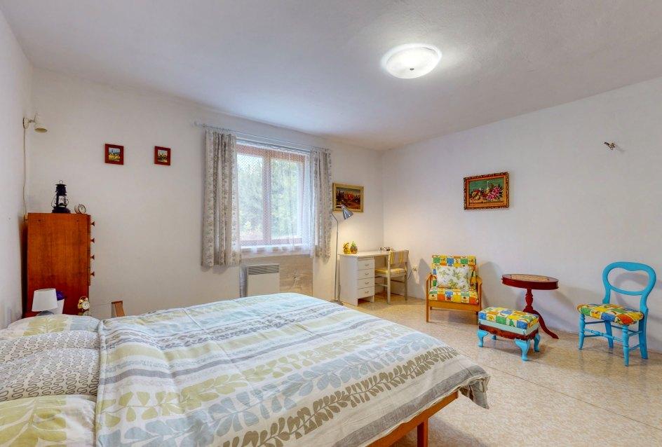 Pohľad na okno, posteľ, stôl a stoličky v spálni